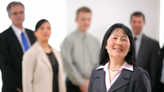 Portrait of Asian business woman with co-workers in background - stock footage