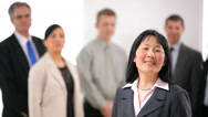 Stock Video Footage of Portrait of Asian business woman with co-workers in background