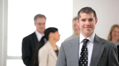 Portrait of business man with co-workers in background - stock footage