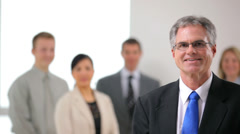 Portrait of mature business man with co-workers in background Stock Footage