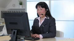 Business woman in office with computer talks on headset Stock Footage
