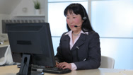 Stock Video Footage of Business woman in office with computer talks on headset