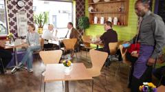 Nuori kahvila ravintola tarjoilija asiakkaiden kanssa Arkistovideo