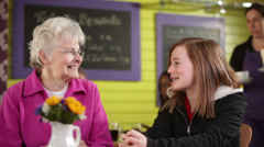 Senior woman with grandaughter in cafe Stock Footage