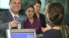 Airport passengers check in at ticket counter Stock Footage