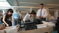 Airport travelers gather belongings after baggage screening Stock Footage