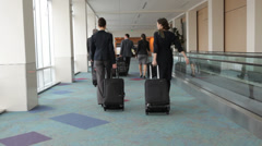 Business people walk through airport with luggage - stock footage