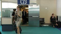Airport passengers walk out of jet way door Stock Footage