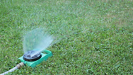 Stock Video Footage of sprinkler watering green lawn
