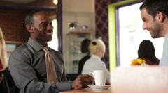 Man and woman meet in cafe.  A relaxed cafe or restaurant setting with man and Stock Footage