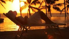 Woman sitting by edge of pool at tropical resort, sunset Stock Footage