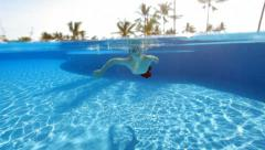 Young boy swimming in pool at tropical resort Stock Footage