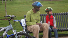 Father and son with bicycles taking a water break Stock Footage