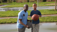 Father teaching son to shoot basketball - stock footage