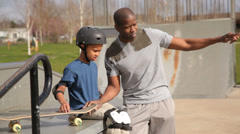 Father and son together at skateboard park Stock Footage