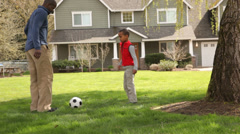 Father and son kick ball in front of family home Stock Footage