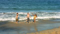 Three kids running at beach, slow motion Stock Footage