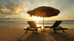 Sunrise at tropical beach with chairs and hut - stock footage