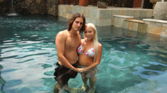 Portrait of couple at tropical resort pool - stock footage