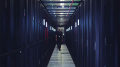 Stock Video Footage of People working in computer server room data center. Walking along rows of super
