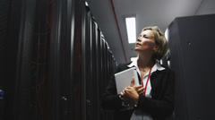 Stock Video Footage of IT businesswoman inspects data center servers. Working in computer server room