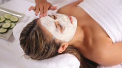 Woman at spa with facial mask and cucumbers - stock footage