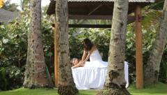 Woman gets massage at tropical resort spa - stock footage