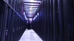 People working in computer server room data center. Walking along rows of super - stock footage