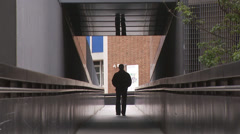 Casually dressed man uses a walkway between the exteriors of two business Stock Footage