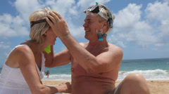Senior couple helping each other with snorkel gear - stock footage