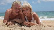 Stock Video Footage of Portrait of senior couple laying in sand at beach