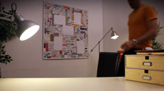 Funny character working late at the office under a desk lamp, puts away his work Stock Footage
