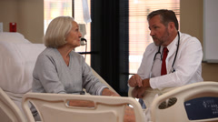 Doctor talks to elderly patient Stock Footage