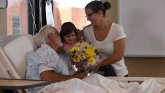 Woman and young girl visit senior man in hospital Stock Footage