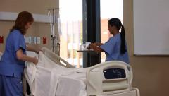 Two nurses making the bed in hospital Stock Footage