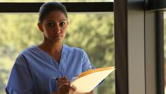 Portrait of nurse holding clipboard - stock footage