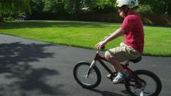 Young boy riding bicycle in driveway, tracking shot - stock footage