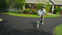 Young boy riding bicycle in driveway, tracking shot Stock Footage