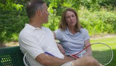 Mature couple outdoors take a break from playing tennis Stock Footage