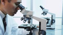 Scientist looks into microscope, dolly movement - stock footage