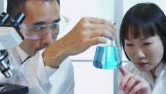 Scientists in lab looking at beaker of liquid - stock footage