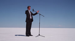 Businessman speaks into microphone at salt flat. Stock Footage