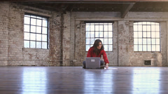 A  young woman sets up her office in an empty loft room. Portrait of a young - stock footage