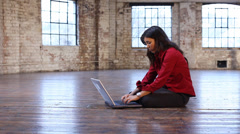 A  young woman sets up her office in an empty loft room. Portrait of a young Stock Footage