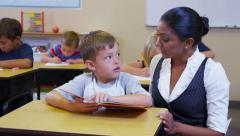 Elementary school teacher helps student read book - stock footage