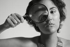 Female portrait with magnifying glass Stock Photos