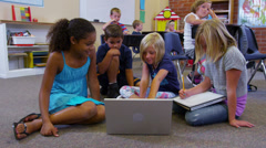 Elementary school students look at laptop computer together Stock Footage