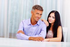 Happy beautiful couple sitting at the table at home Stock Photos