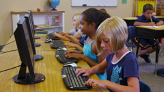 Elementary school students work with computers - stock footage