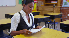 Elementary school teacher grading papers Stock Footage